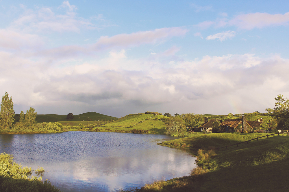Retreating stormclouds and a rainbow over Hobbiton lake and the Green Dragon Inn.