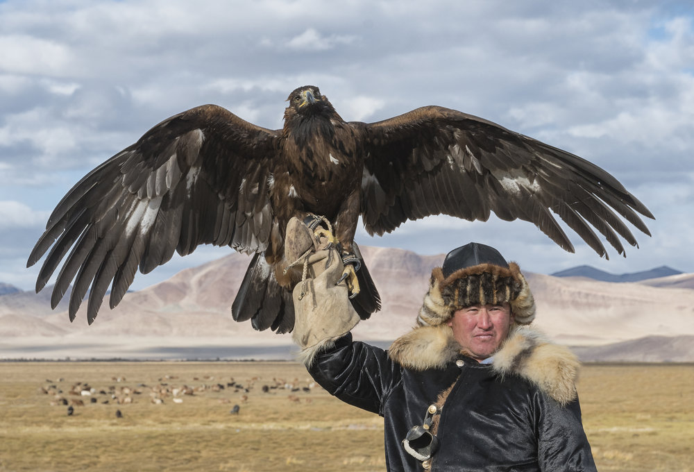 eagle hunter raising eagle above his head.jpg