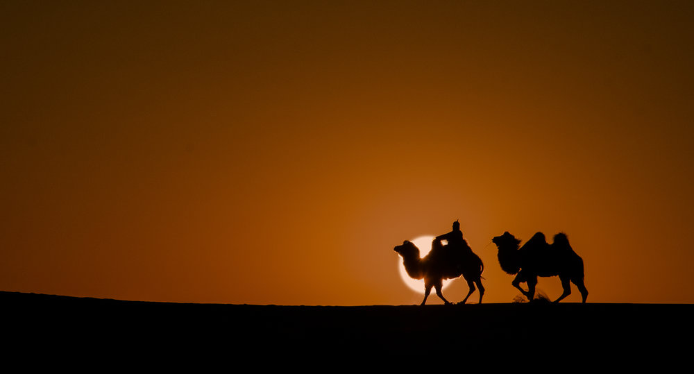 Camel herders wander on the top of the sand dunes as the sun sets.
