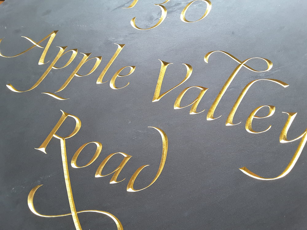 Address Sign - The beauty of lettercarving by hand is arguably best expressed with gilded letters on black slate. This address sign was installed in an area where easy legibility was of the utmost concern, so the striking contrast of gold on black won the day.