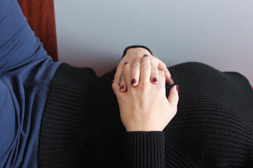 Hands loosely folded across abdomen