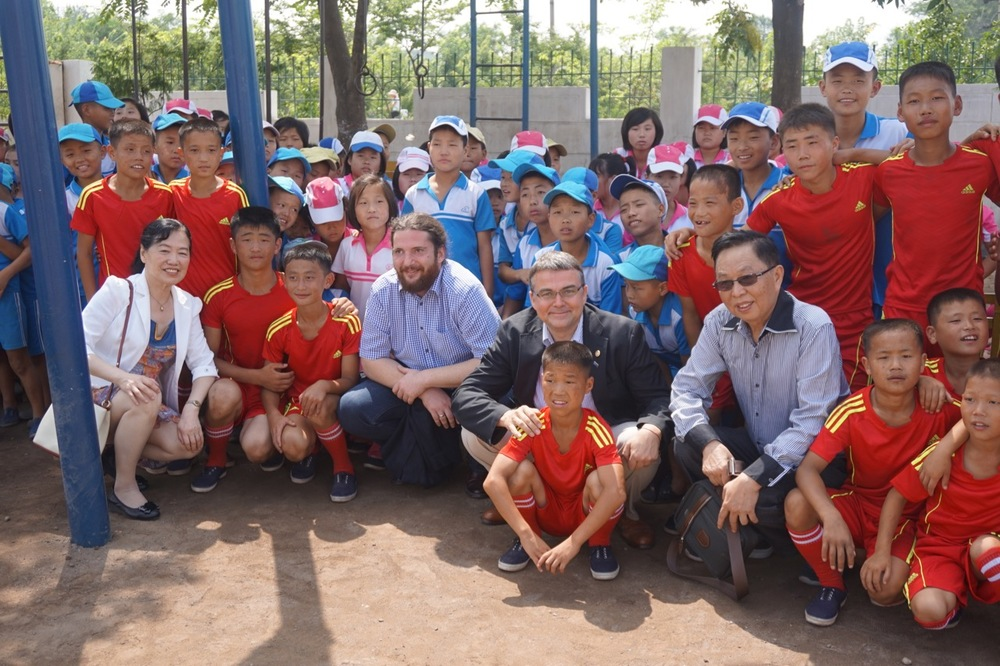 Rotarians Randal and NIkola along with Dr. Chen Qun and Shen Keqiao say farewell to the students and football players at Mirim School.
