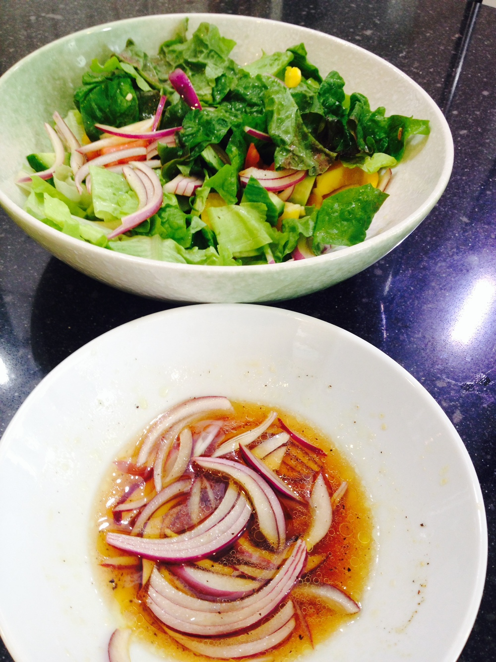 The red onion is soaking up the goodness from the dressing before getting tossed in the big bowl of salad.