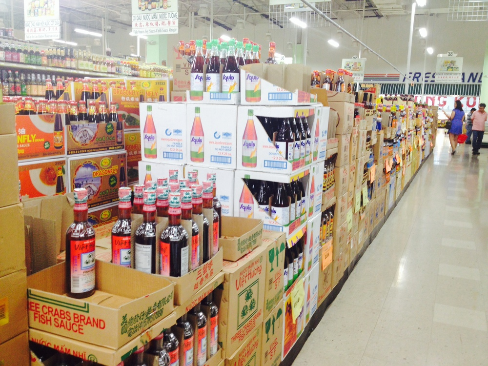 "This is the Fish Sauce ""on-sale"" aisle with more than 25+ brands to choose from, but you'll see that the two most popular are right in the front, Three Crabs and Squid brands."