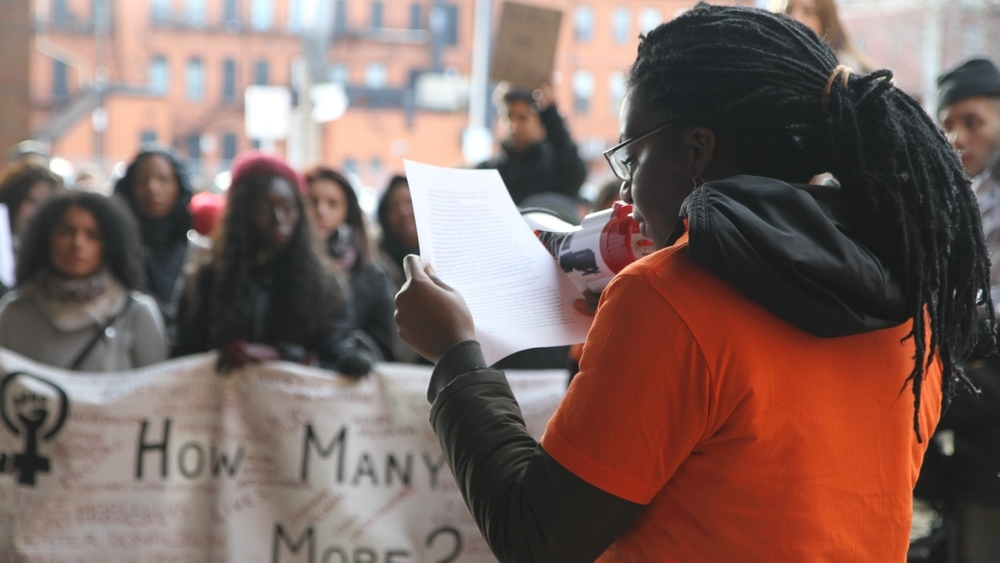 Organizers of an anti-racism march on Dec. 1, 2014 met with Hamilton Police and heard confirmation the service collects information from people officers stop on the street. Here, Kayonne Christy, read a list of demands the group submitted to the police that day. (Kelly Bennett/CBC)