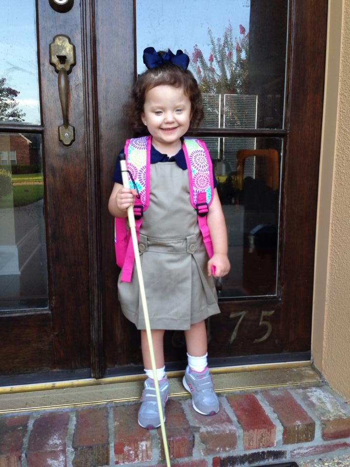 Addison, holding her cane, poses for a picture on the first day of school