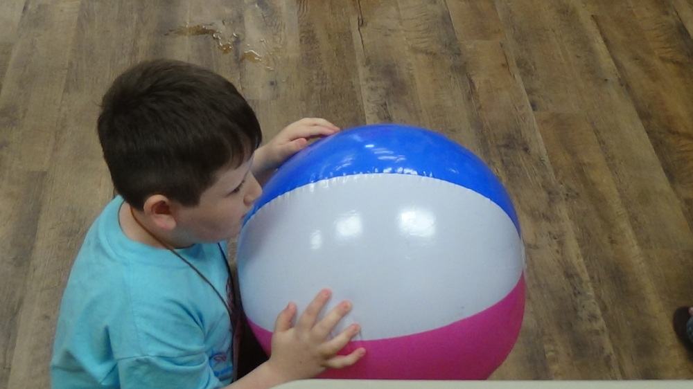 Strider searches for his braille letter to call out during a beach ball game