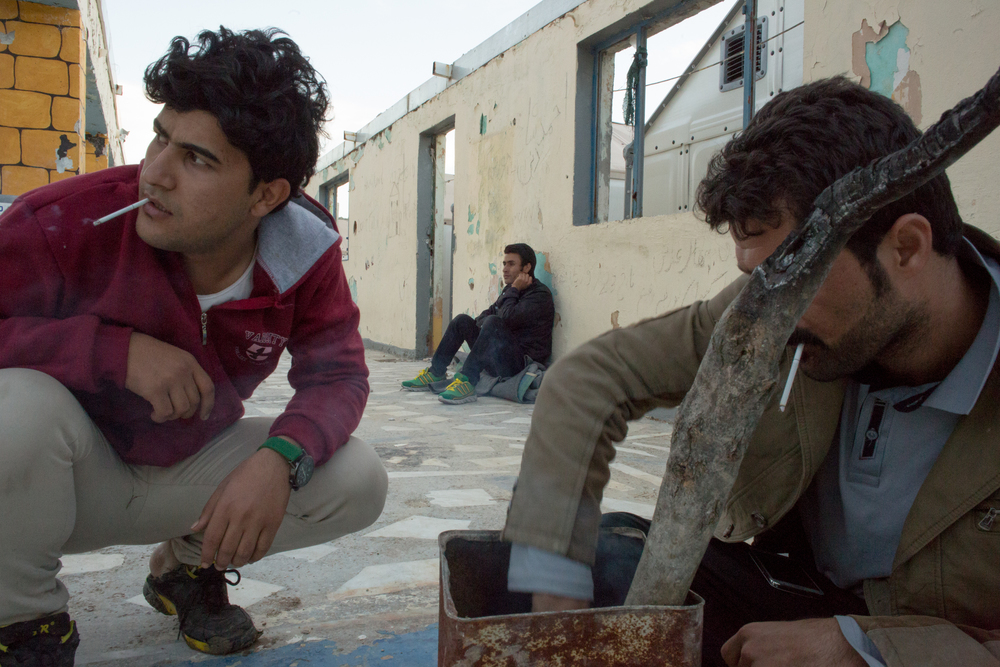 Three young Syrian men gather to start a fire in an abandoned building inside the Moria registration camp on Lesvos. Single men are often required to wait longer to register than families and are not provided with the limited shelter that is designated for women and children.