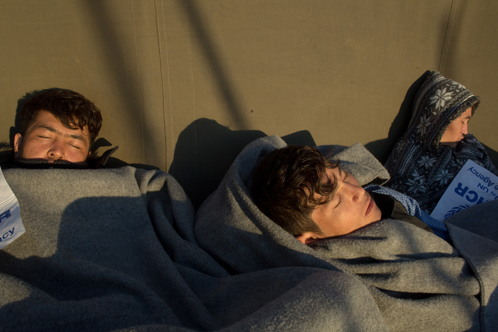 Three young refugees sleep near the bus loading area at the Oxy transit camp on Lesvos. Families are given priority when loading buses bound for the registration centers at the south of the island and young men are often asked to sleep outside until more buses arrive the next morning.