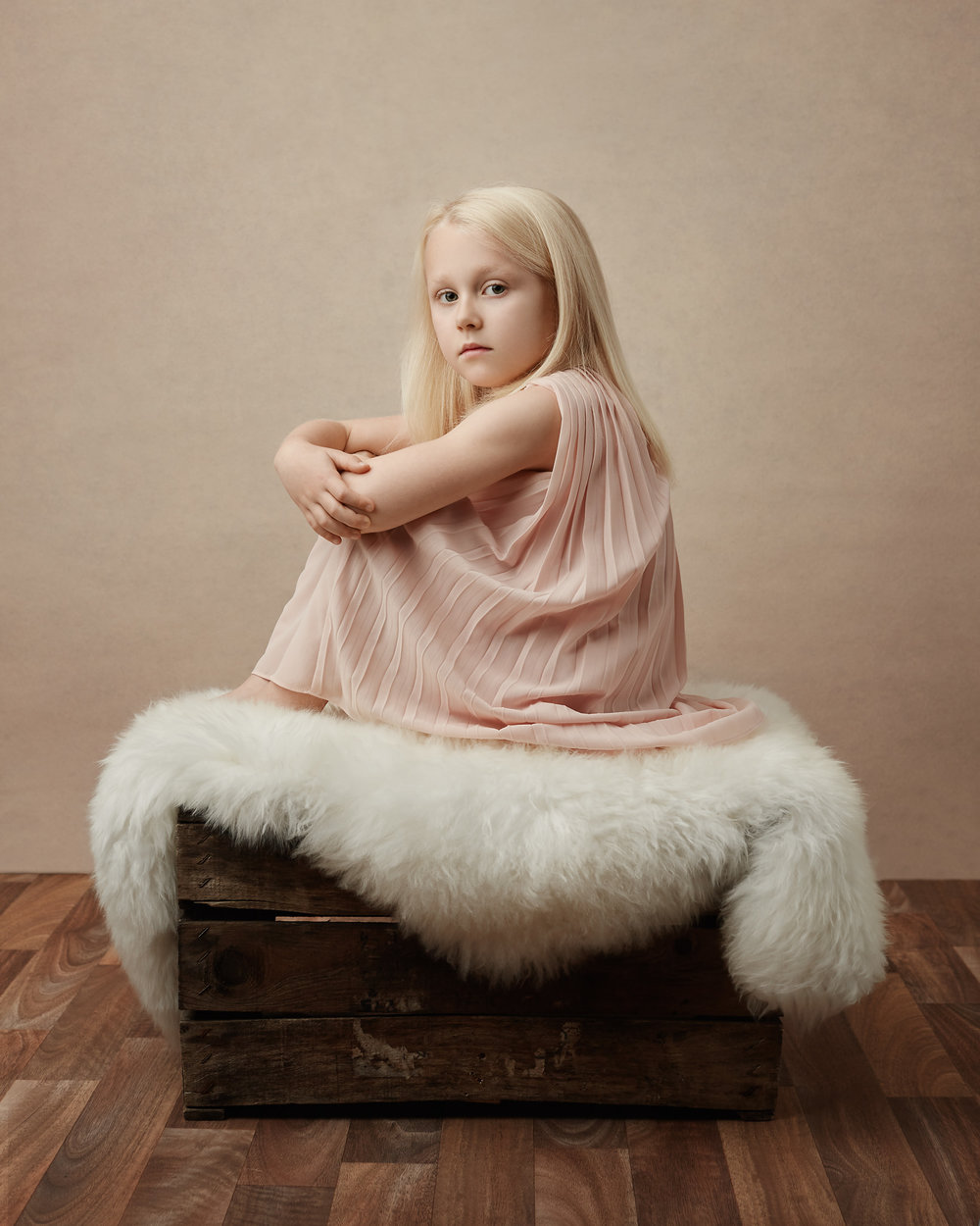 Lily sitting on sheepskin rug