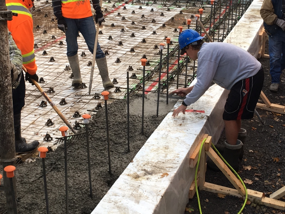 Concrete pour -- hand troweling near the wall rebar