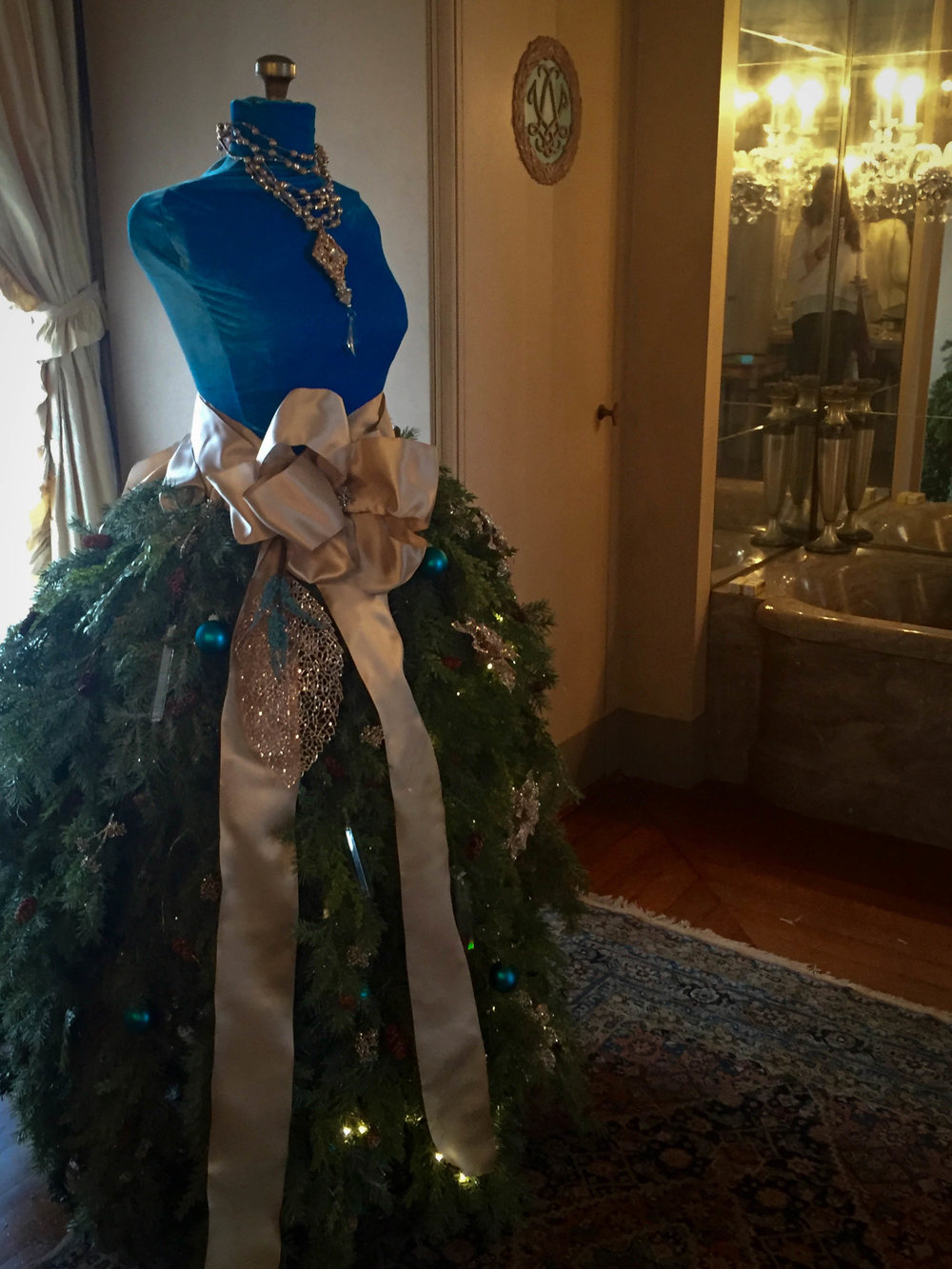 Constructed of chicken wire,  greenery, pine cones, crystals and Christmas ornaments.  A blue velvet mannequin cover was created to match the colors in Mrs. V's dressing room.