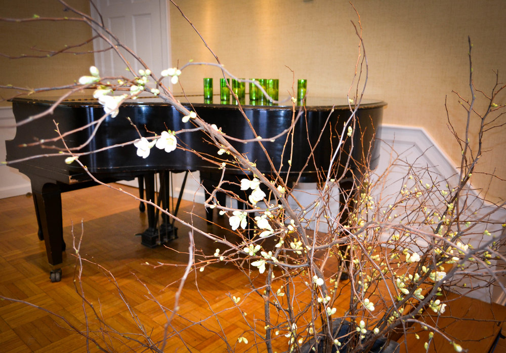 Tall quince branch arrangements grace the presentation area and a local pianist played for the guests.