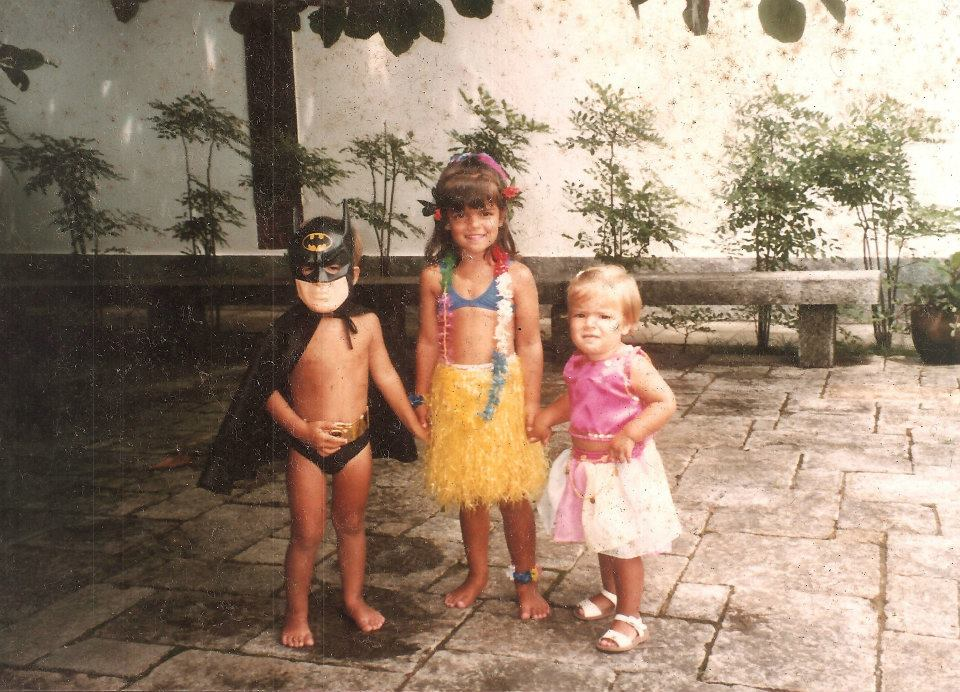 A young Ana (middle) with her brother and sister preparing for Carnival.