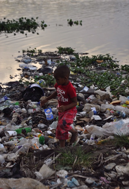 Young boy looking through trash in a heavily polluted area within his neighborhood. Global Incite Dominican Republic Spring Break Trip 2015