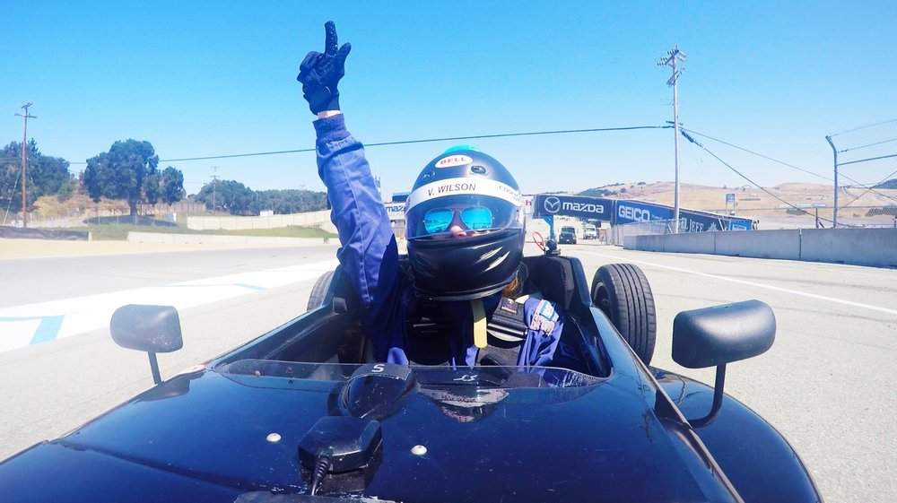 If racing formula 1 cars around an iconic racetrack isn't enough to get your blood pumping, try doing it one-handed!