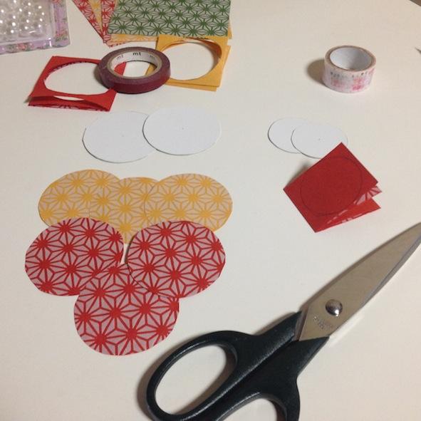Découper des ronds dans le papier japonais en pliant plusieurs fois une bande de papier. Il faut 4 cercles pour faire 1 décoration.