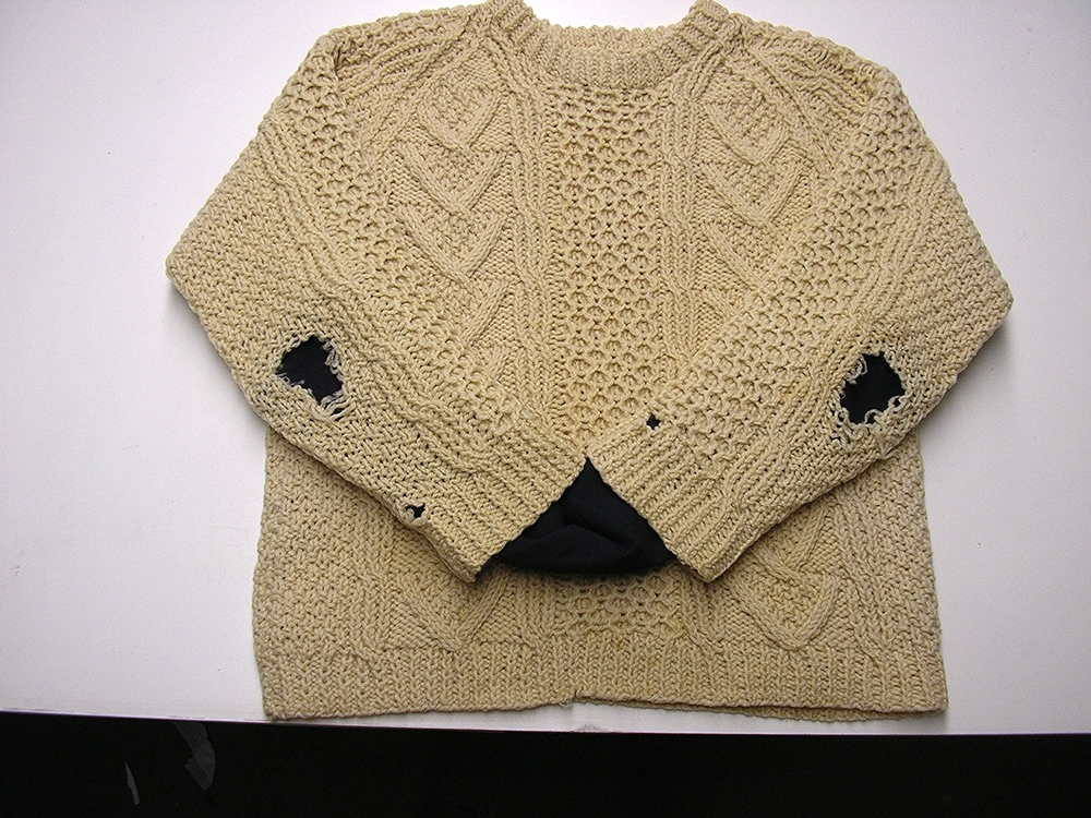 This Aran child's sweater, much loved (and well worn!) had multiple stains and holes with the elbows needing complete re-knitting to close the massive holes.