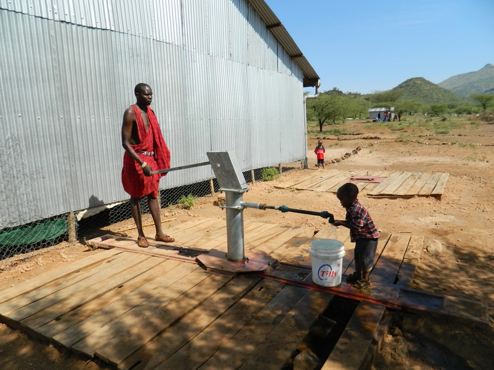 Maasai Man begins to pump water for the community.