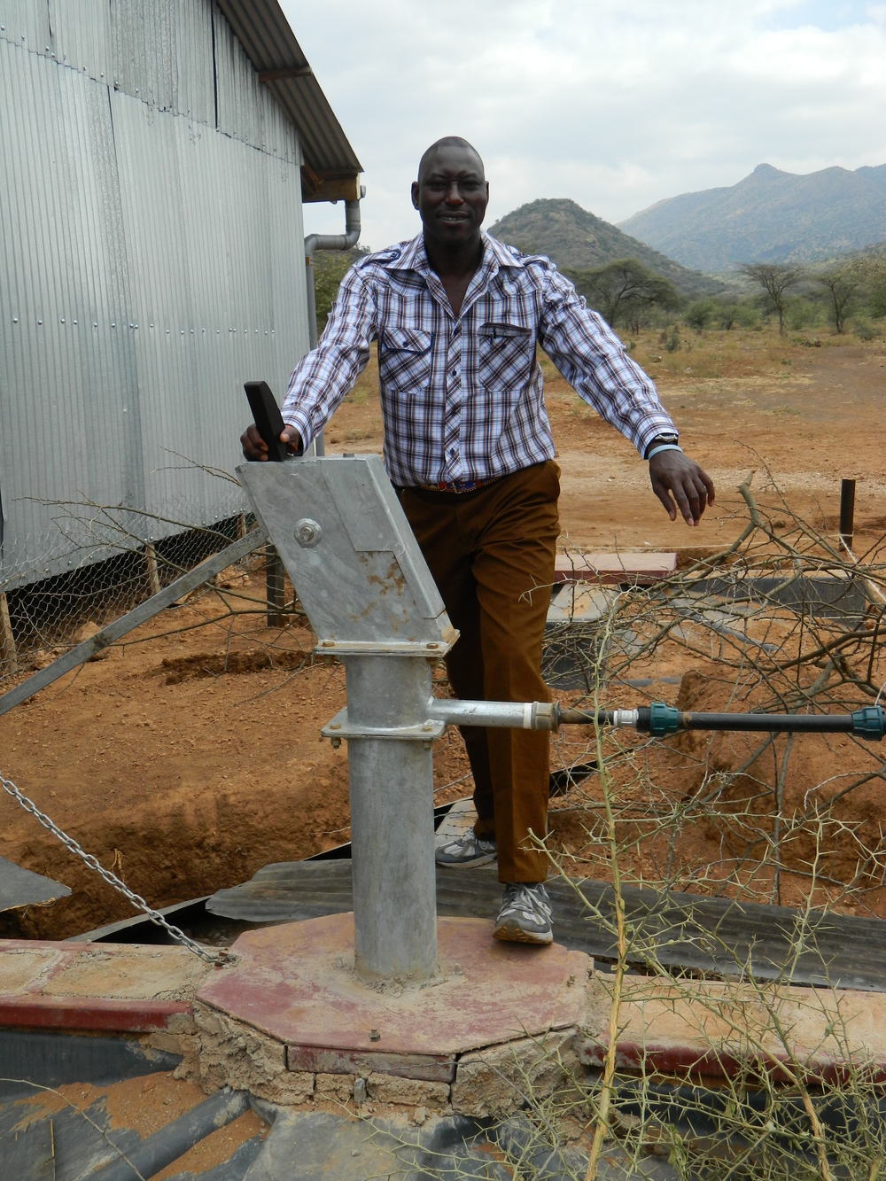 Pastor Peter proudly examines the pump.