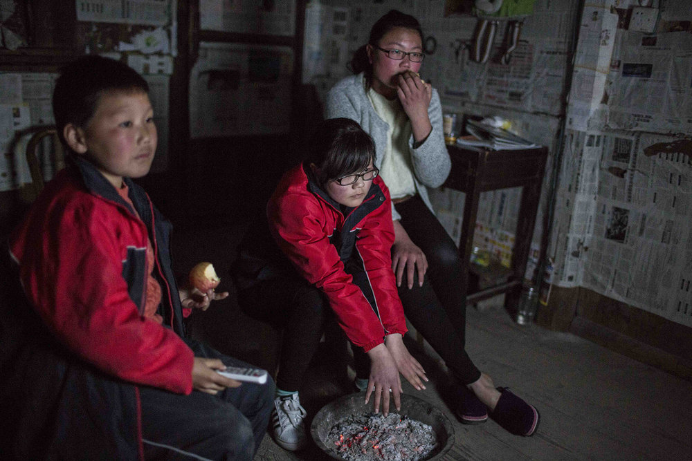 "From left, Jinhao Ma, 9, Leting Ma, 16, and Meiting Ma, 17, watch television after dinner at their grandmother's house. Watching TV is the only entertainment they have on weekends. They live in the Mashang Mountain area of Wenzhou, China, where the temperature at night drops below 50 degree Fahrenheit in late March. They put leftover coals in a large basin to keep themselves warm at night. The Ma children are among China's ""left-behind"" kids. Their parents are in Shanghai, 250 miles away from Mashang Mountain, working in a breakfast shop to make enough money to raise them."