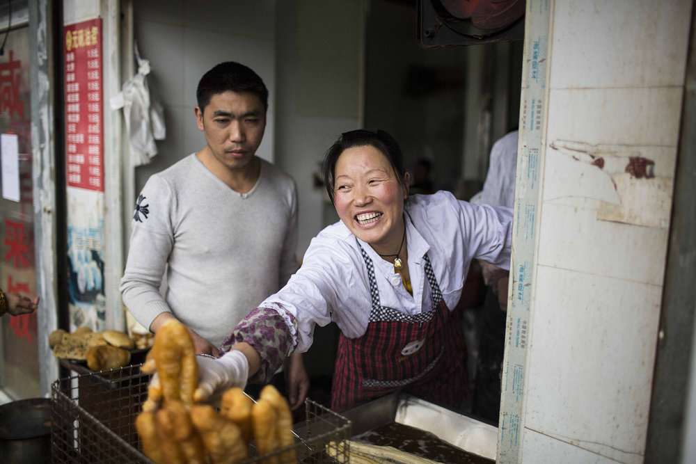 Zhu grabs one fried bread stick to make sticky rice roll as she talks to customers.