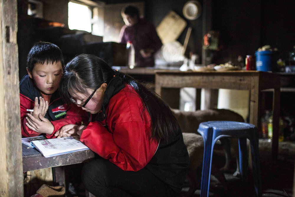 Leting Ma helps her little brother do his first-grade math homework while they wait for lunch.