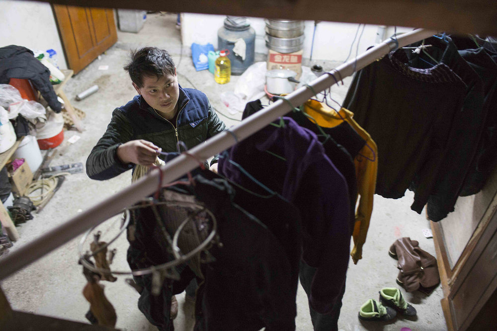 Guocheng Ma hangs up clothes on a bamboo rack inside the house before a family trip down the mountain. His children need to return to school, while he and his wife need to find a new location for their breakfast business.