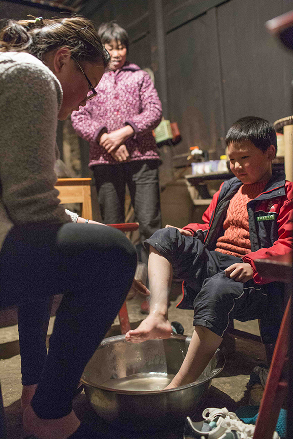 Meiting Ma, the eldest of the three children, washes her younger brother's feet before they go to bed.