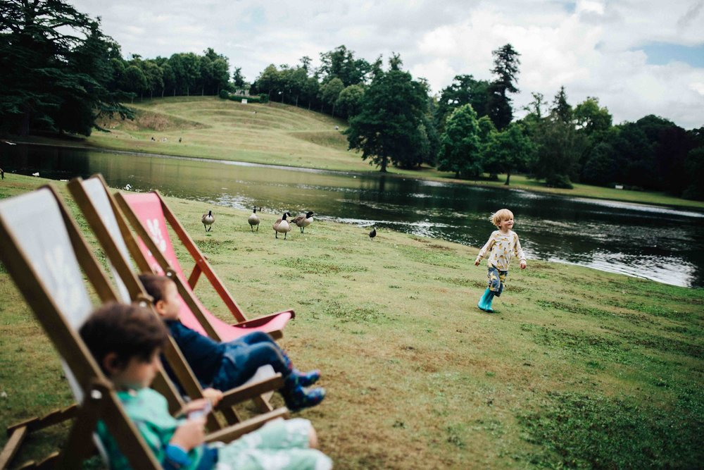 Boy running by lake near geese while other boys are sitting in deck chairs at Claremont Landscape Gardens during family photoshoot