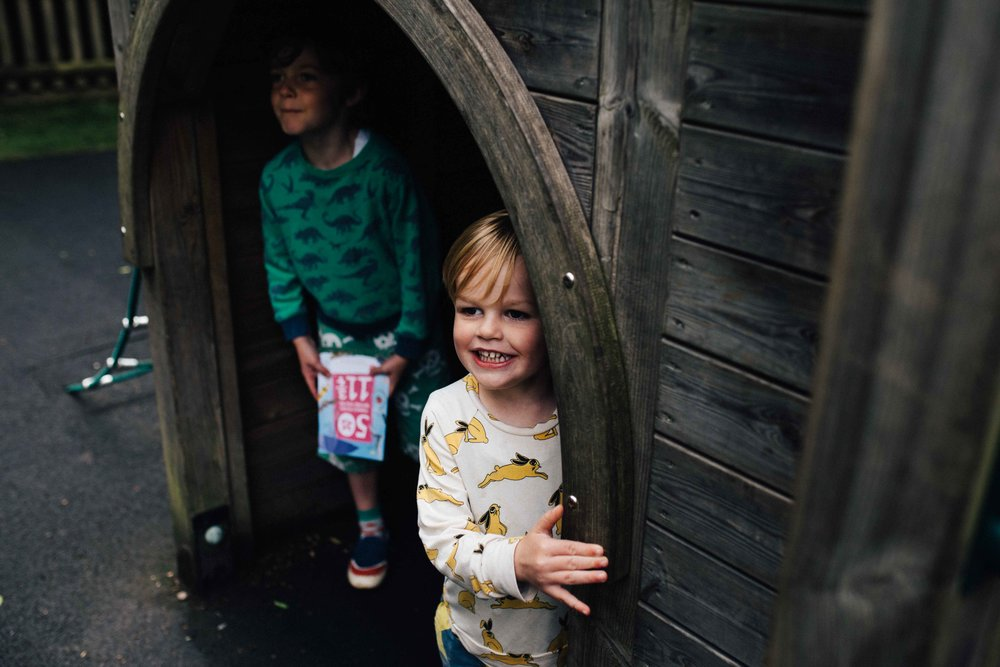 Boys hiding under castle in play area in Claremont Landscape Garden, Surrey, during family photo session