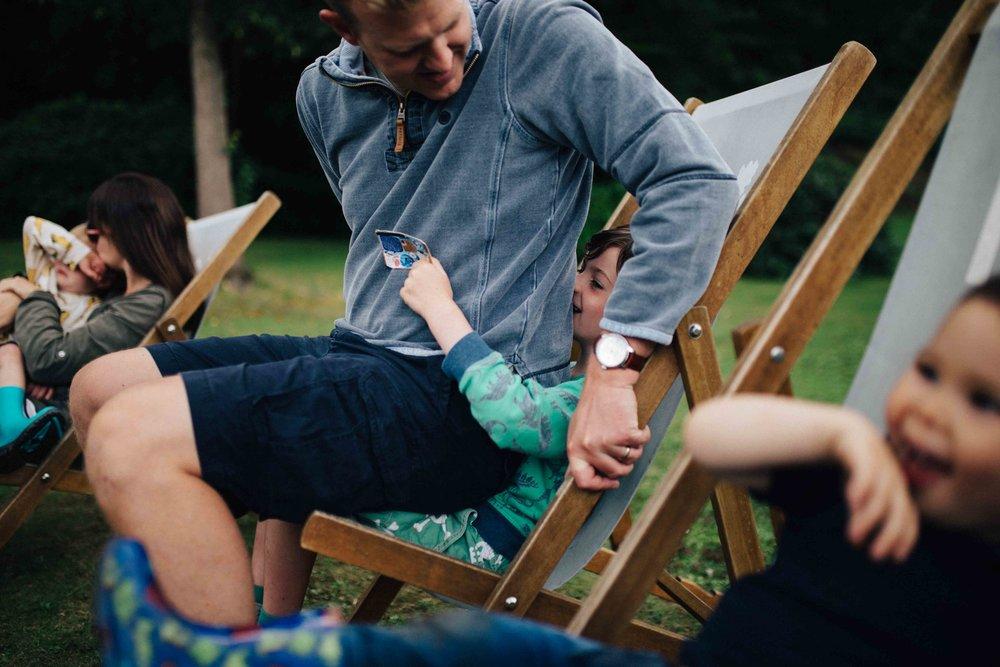Dad sitting on boy in deck chair at Claremont Landscape Garden