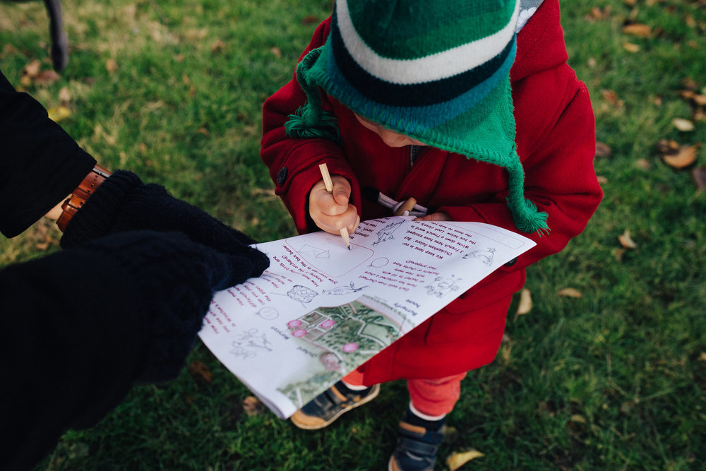 Toddler boy writing on paper at Chartwell House's Christmas trail