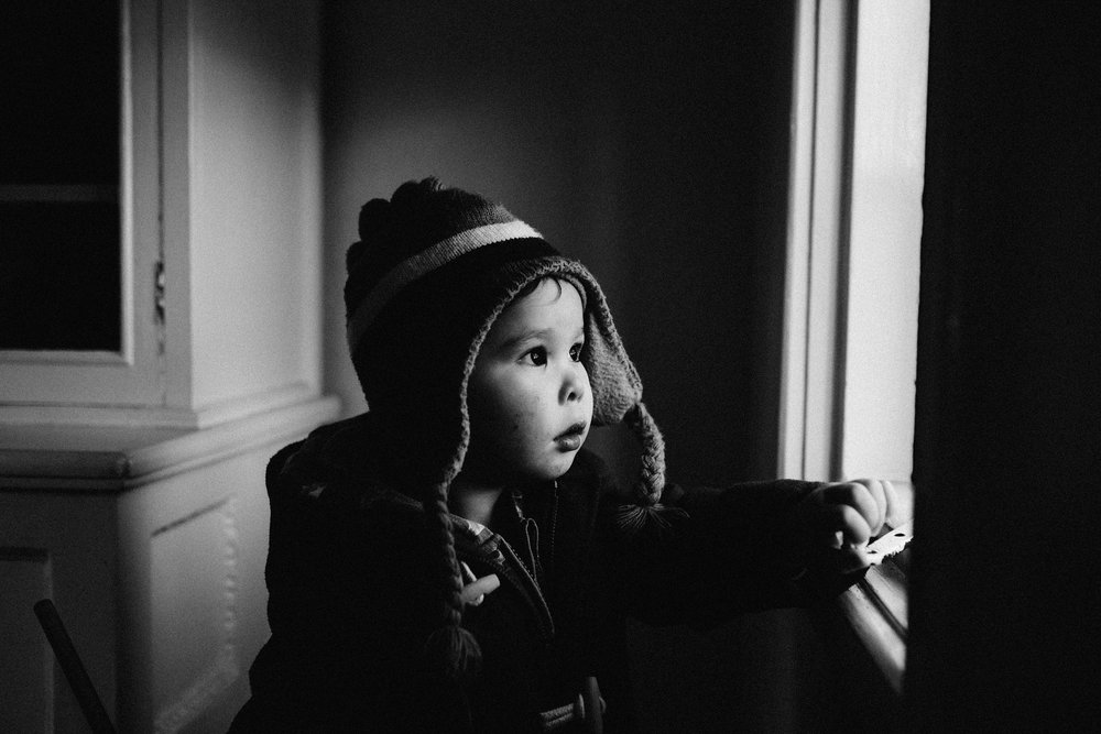 Black and white photo of young child looking at the window at Chartwell House, Kent