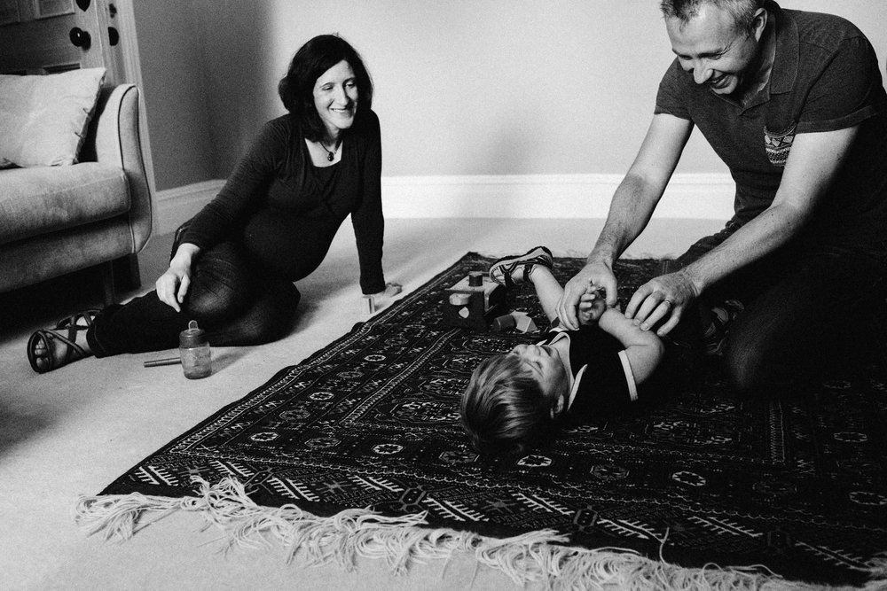 Dad tickling little boy with mum smiling during newborn and family photoshoot in Bromley near London