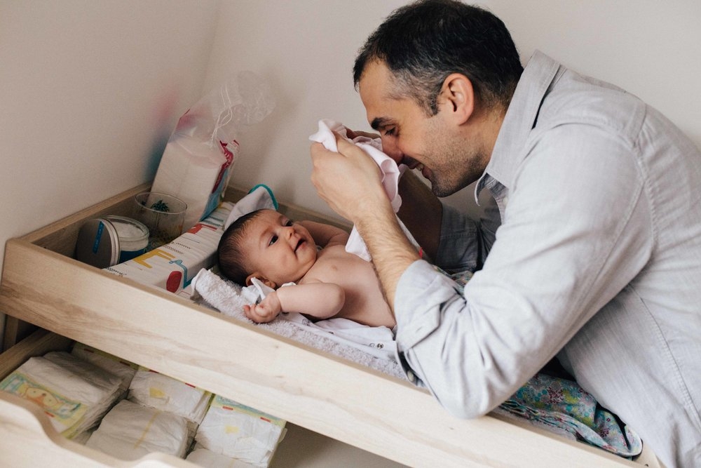 Father playing with little baby girl while dressing her up during baby photo session in London
