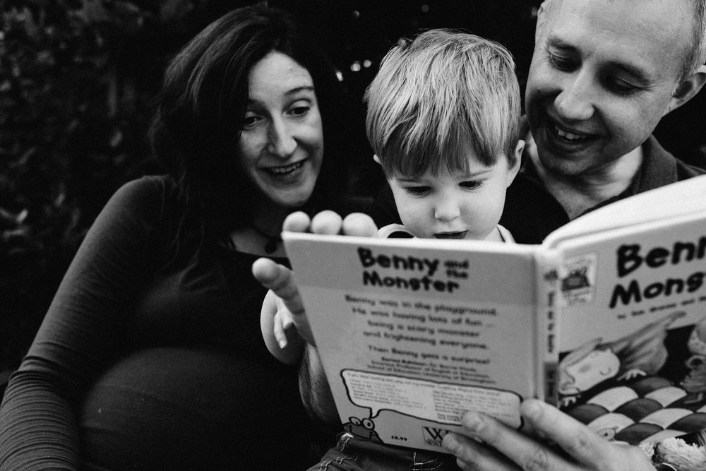 Father reading story to boy next to mother during newborn and family photoshoot