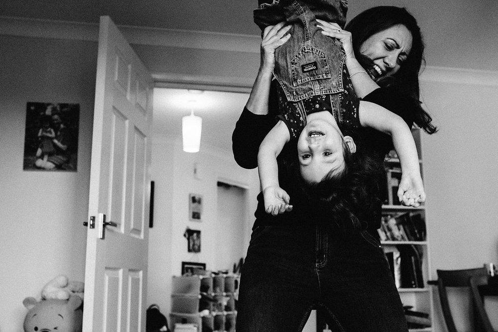 Mum holding daughter upside down