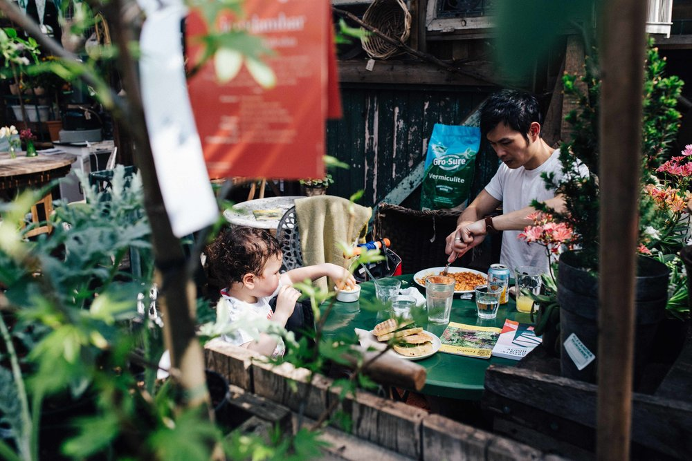 Little boy and father eating at Alexandra Nurseries in Penge, South East London