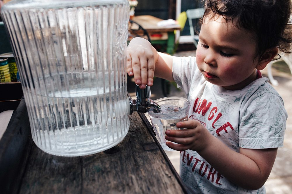 Child pouring water at at Alexandra Nurseries, Penge, South East London during children family photo session in South East London