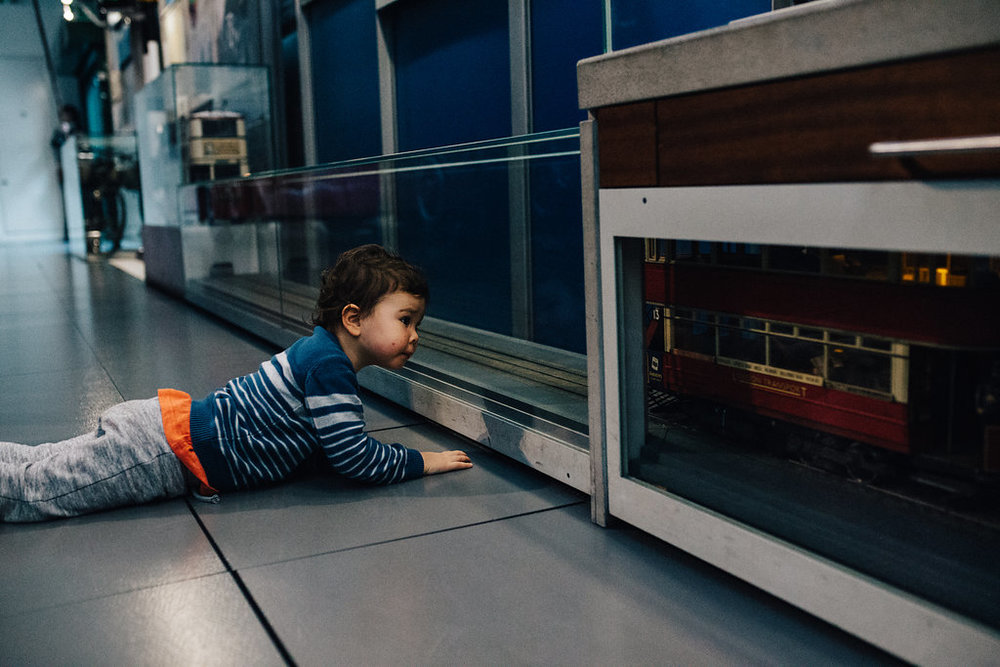 Child lying on floor looking at small trains at London Transport museum