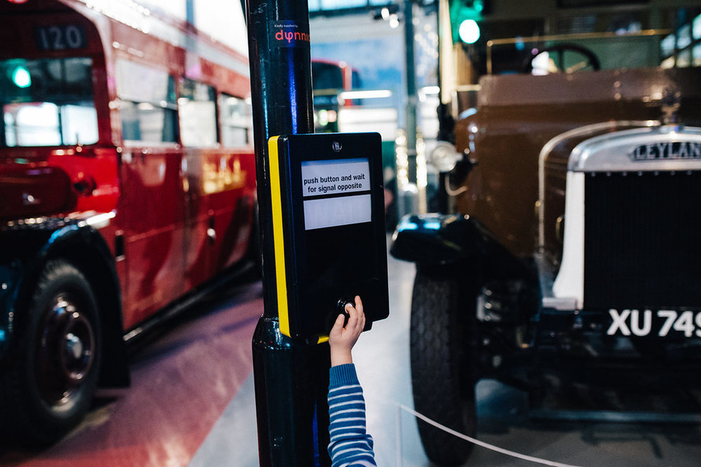 Child pressing a traffic light button at London's Museum of Transport during children photography photoshoot
