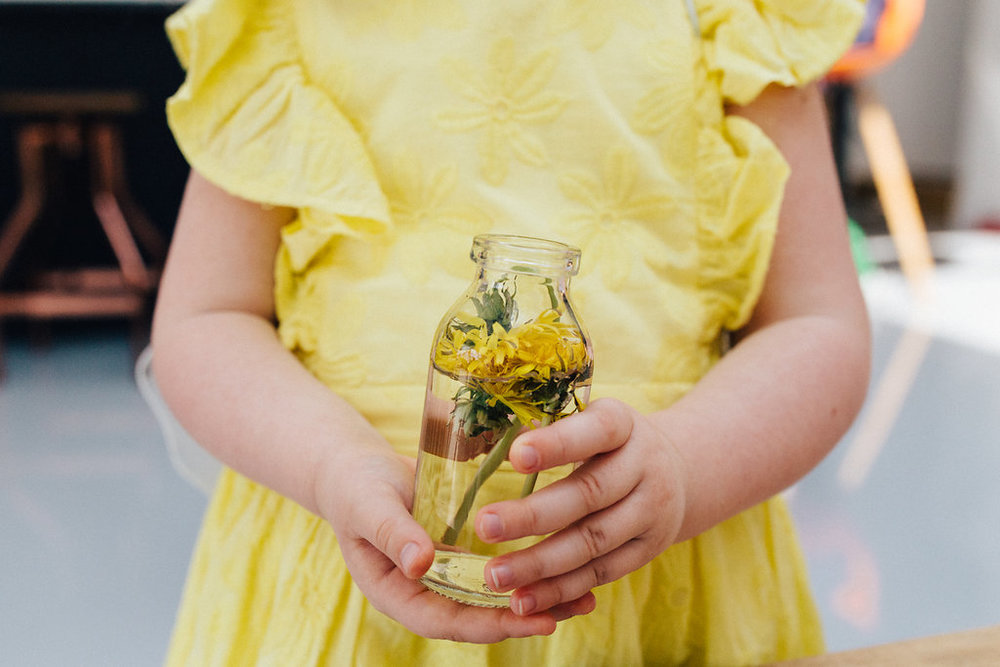 Little girl in yellow dress holding a small vase with a yellow flower during family photoshoot near London