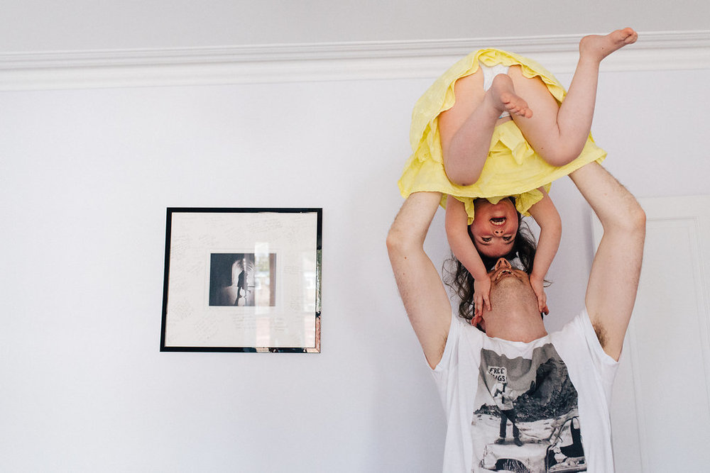 Dad holding daughter in the air during family photoshoot near London by Marion & You Photography