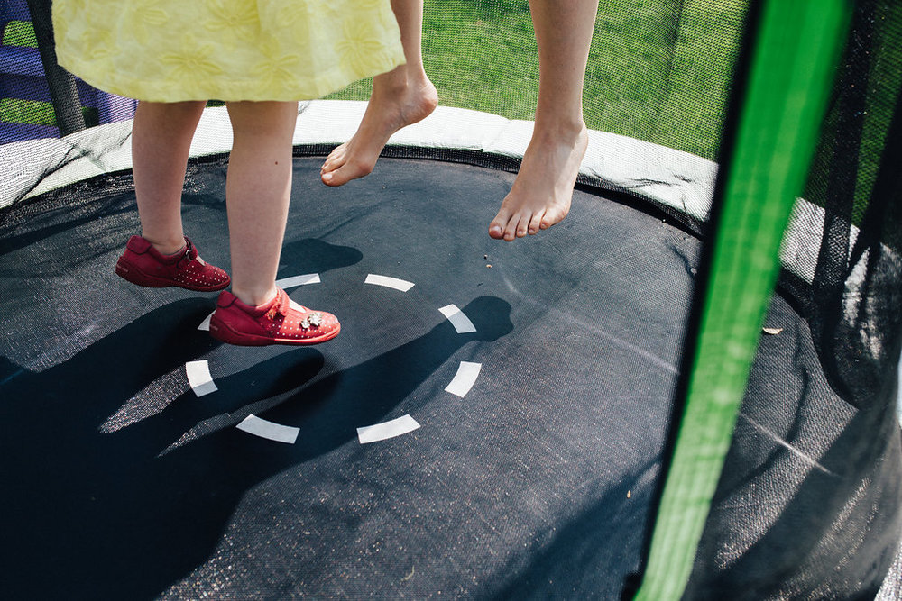 Feet of mum and daughter jumping on trampoline during family photo session near London