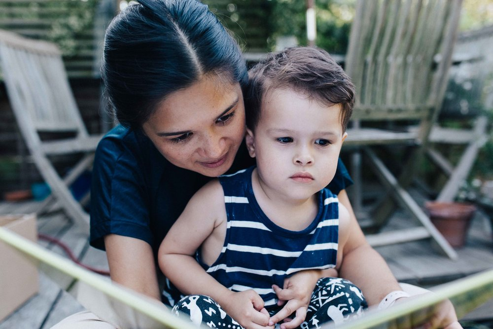 Mother sitting down with young child on her lap reading a book