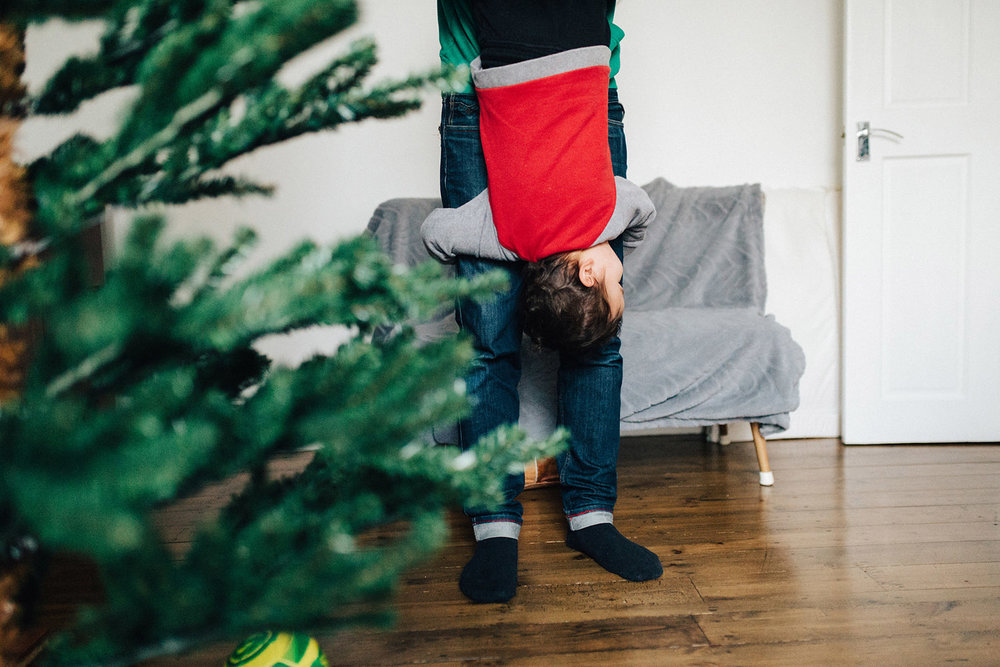 Dad holding boy down next to Christmas tree