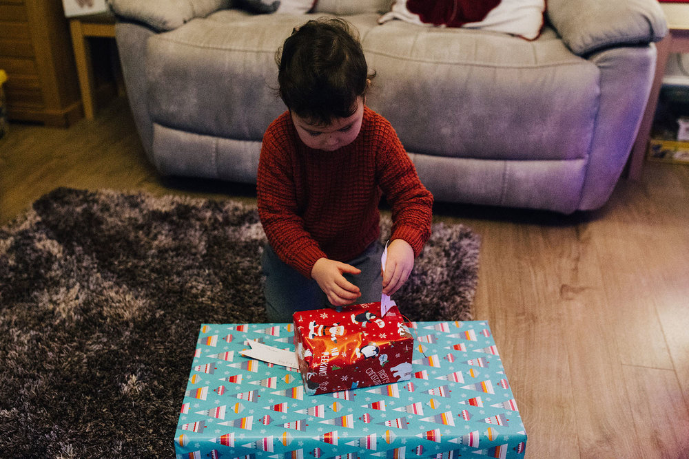 Boy unwrapping Christmas presents