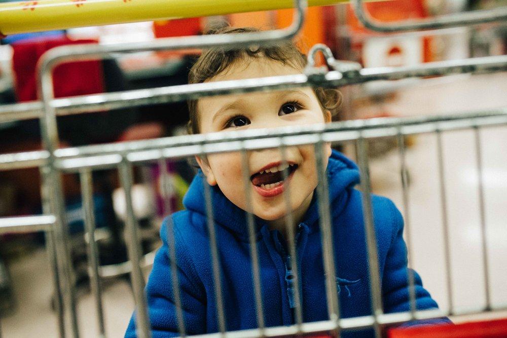Boy smiling through shopping trolley