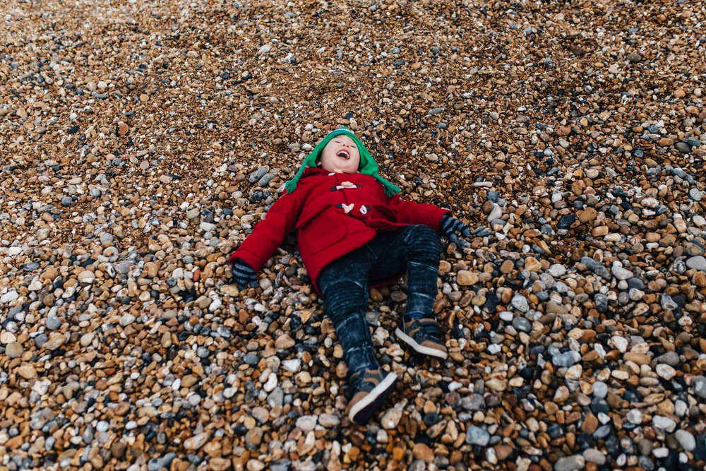 Boy laughing and lying down on pebble beach